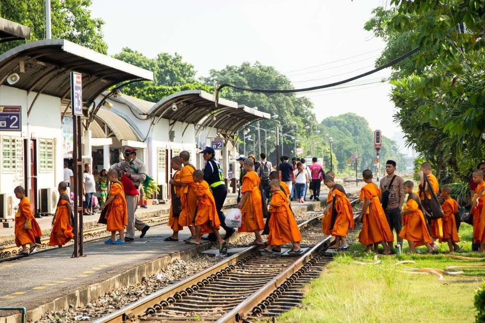 Novices back from field trip walk across railroad at Bang Sue railway station in Bangkok. Ton Bangkeaw/Shutterstock
