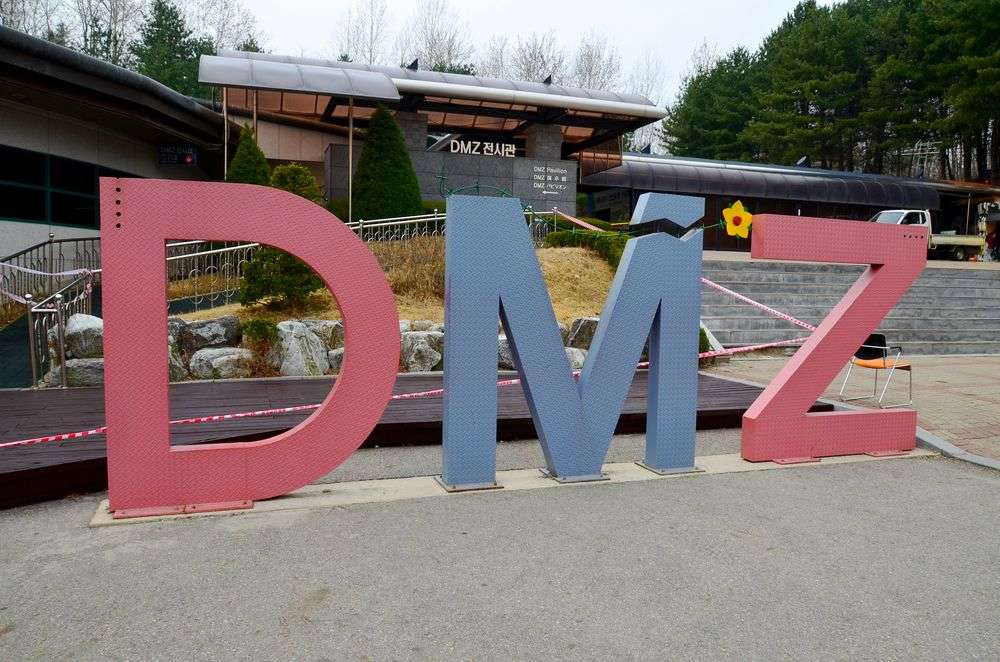 DMZ sign in Paju, South Korea. The Korean Demilitarized Zone is a strip of land running across the Korean Peninsula that serves as a buffer zone between North and South Korea. meunierd/Shutterstock